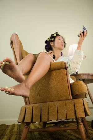 spiraling: Asian woman in curlers looking in mirror LANG_EVOIMAGES