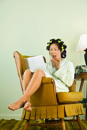 legs wide open: Asian woman in curlers looking at laptop LANG_EVOIMAGES