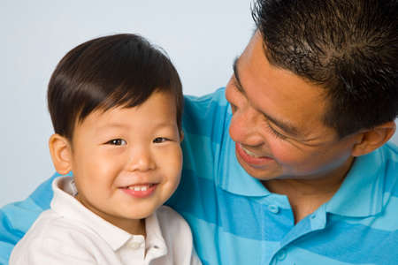 age 40 45 years: Asian father smiling at son LANG_EVOIMAGES