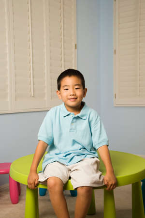 misbehaving: Asian boy sitting on table LANG_EVOIMAGES