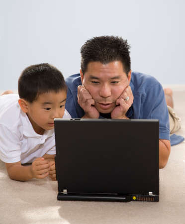 age 40 45 years: Asian father and son looking at laptop