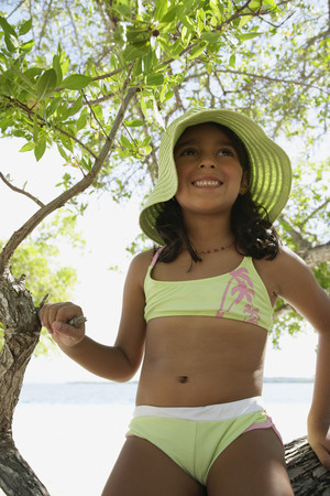 only one girl: Hispanic girl in bathing suit under tree