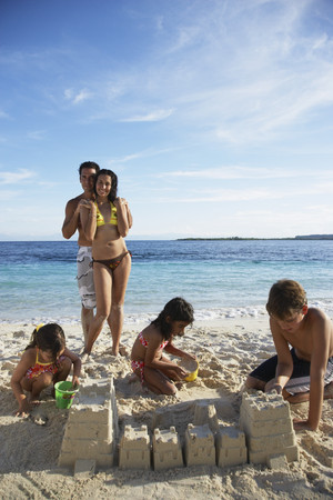 togs: Hispanic family building sand castle