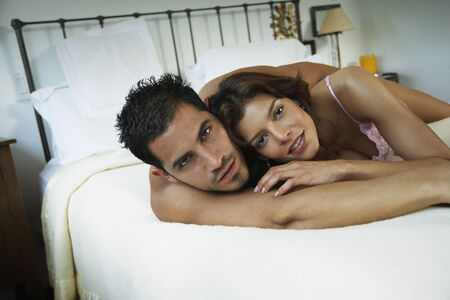 mate married: Hispanic couple hugging in bed LANG_EVOIMAGES