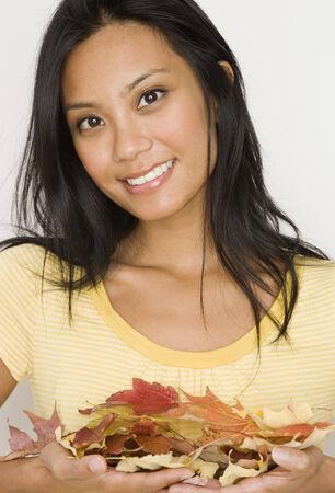 islander: Pacific Islander woman holding autumn leaves