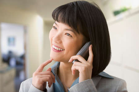 acknowledging: Asian businesswoman talking on cell phone