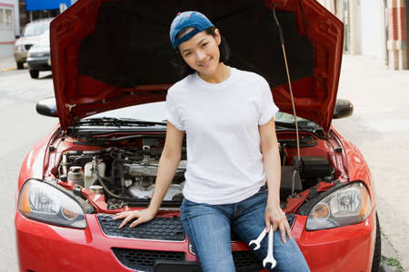 motioning: Asian woman holding wrenches next to open car hood LANG_EVOIMAGES
