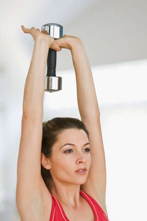 unwholesome: Woman lifting weights LANG_EVOIMAGES