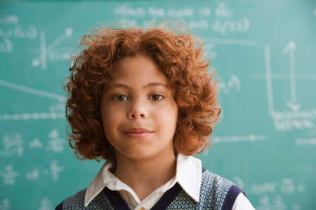 bestowing: Mixed Race boy standing in front of blackboard
