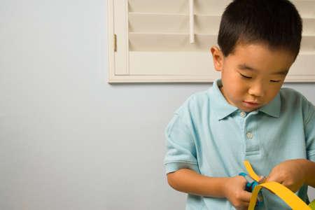 cherishing: Asian boy cutting paper