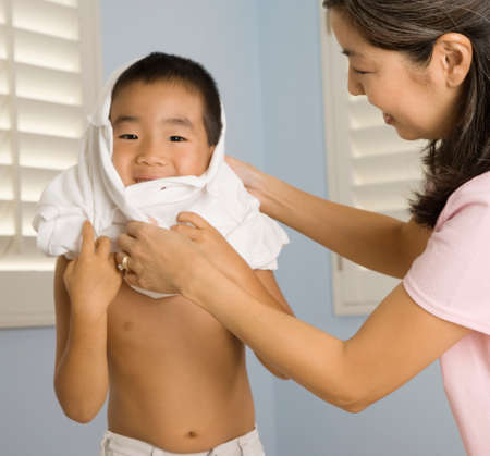 spectating: Asian mother helping son put on shirt