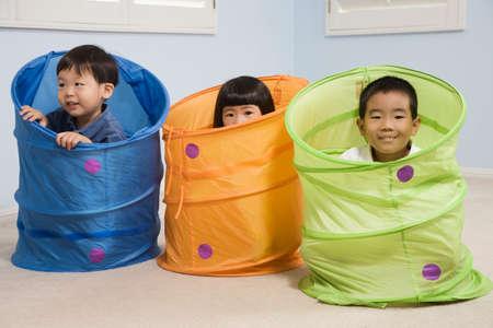 playthings: Asian siblings playing in tubes