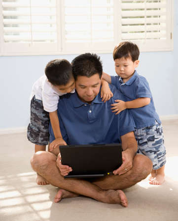 fathering: Asian father and sons looking at laptop