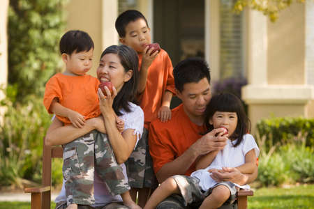 age 40 45 years: Asian family eating apples on bench