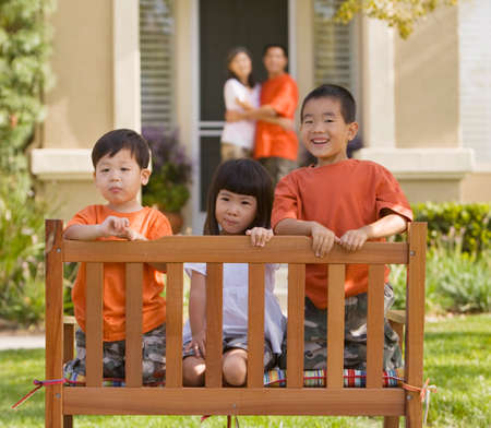age 5: Asian siblings sitting in bench