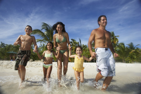 Hispanic family running into water Stock Photo