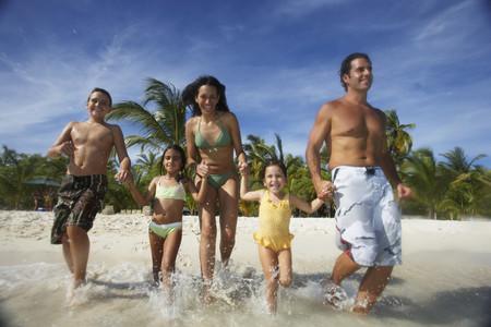 Hispanic family running into water Archivio Fotografico