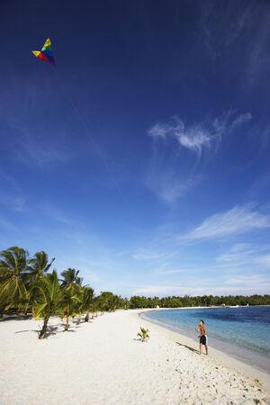 ヒスパニック系の少年がビーチでカイトを飛行