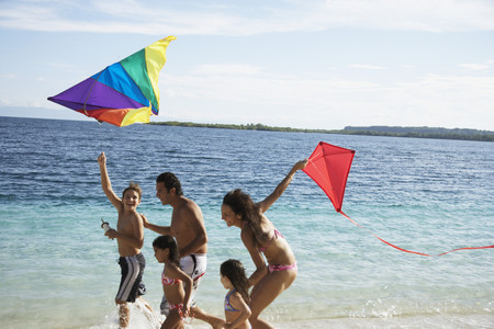 Hispanic family flying kites at beach Foto de archivo
