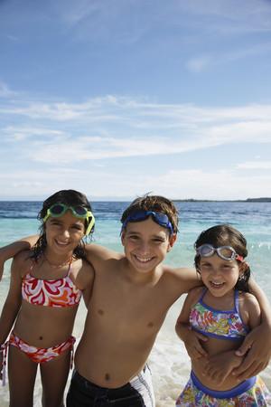 bathingsuit: Hispanic siblings hugging at beach