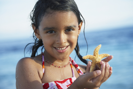 togs: Hispanic girl holding starfish