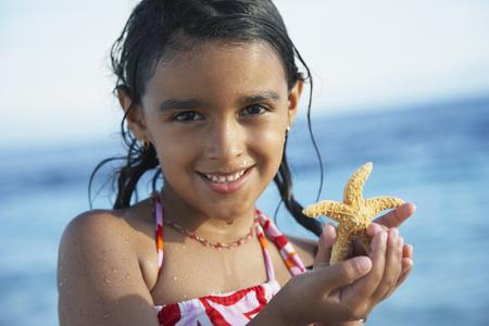 bathingsuit: Hispanic girl holding starfish