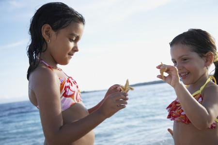 lighthearted: Hispanic sisters holding starfish