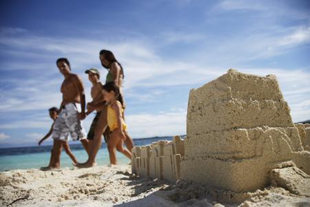 saturating: Hispanic family walking past sandcastle
