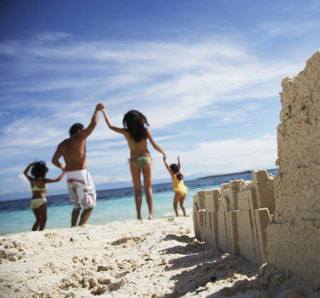 kids holding hands: Hispanic family with sand castle in foreground LANG_EVOIMAGES