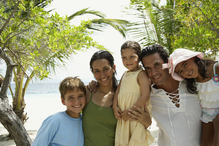 age 5: Hispanic family hugging at beach