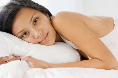 wearying: Pacific Islander woman laying on bed