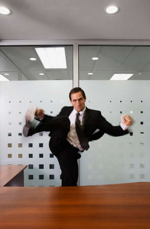 between 30 and 40 years: Businessman kicking over desk