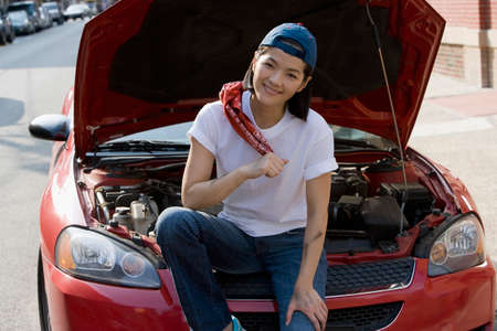 tomboy: Asian woman sitting next to open car hood