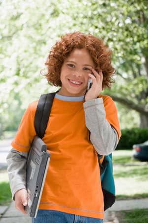 sidewalk talk: Mixed Race boy talking on cell phone