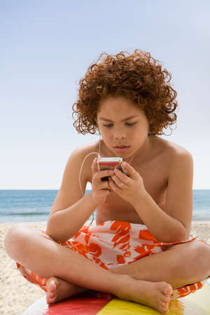 slumbering: Mixed Race boy listening to mp3 player on surfboard LANG_EVOIMAGES