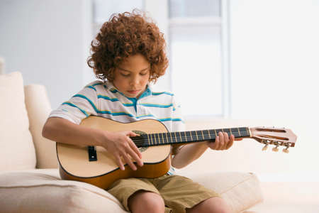 boy playing guitar: Mixed Race boy playing guitar