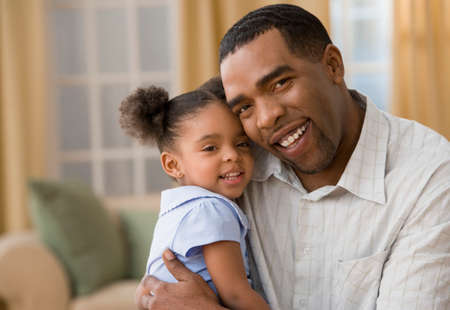 unyielding: Mixed Race father and daughter hugging