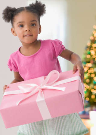 immense: Mixed Race girl holding gift LANG_EVOIMAGES