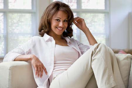 searcher: Hispanic woman sitting on sofa
