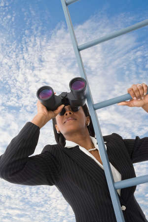 scaling ladder: African businesswoman looking through binoculars on ladder
