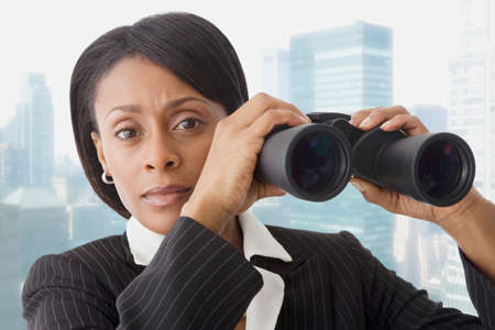 business attire teacher: African businesswoman holding binoculars