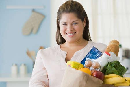 playing on divan: Hispanic woman holding bag of groceries LANG_EVOIMAGES