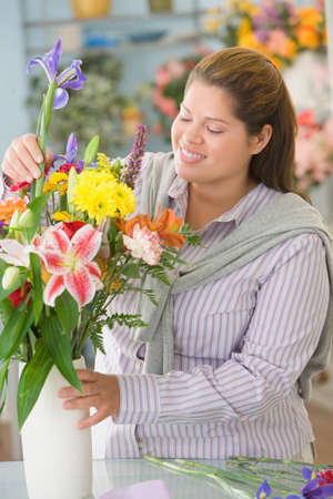 plus sized: Hispanic female florist arranging flowers LANG_EVOIMAGES