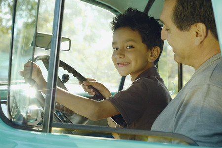 Hispanic father and son sitting in truck