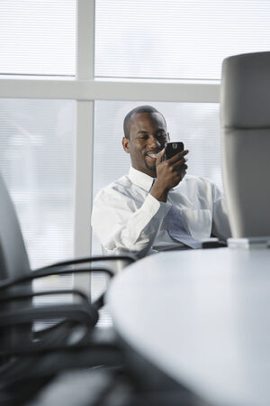 acknowledging: African American businessman looking at cell phone