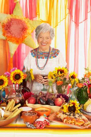 acknowledging: Senior Hispanic woman behind buffet table
