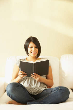 filipino ethnicity: Asian woman reading on sofa