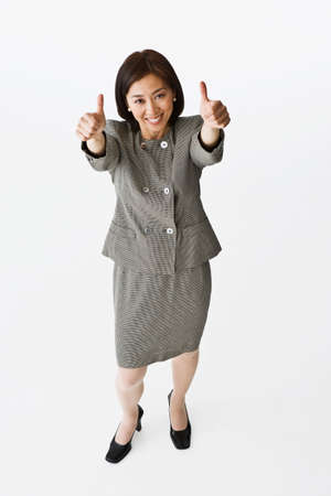 bestowing: Asian businesswoman giving thumbs up LANG_EVOIMAGES