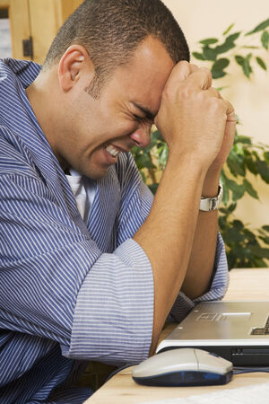 Frustrated Pacific Islander man next to laptop Stock Photo