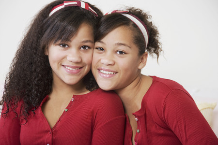 mixed race ethnicity: African twin sisters hugging LANG_EVOIMAGES